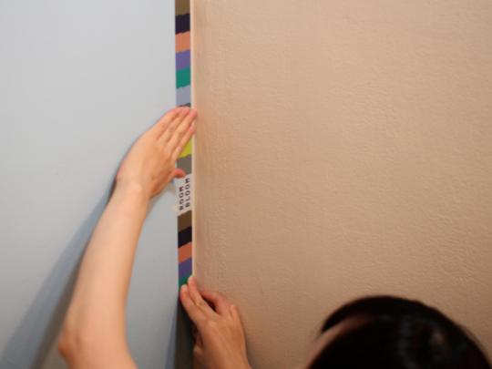 マスキングテープを肩幅位まで広げてから、少しずつ貼っていく。しっかりと手のひらで押さえよう