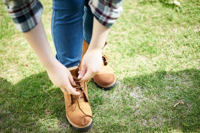 ブーツの靴紐を結ぶ女性のイメージ