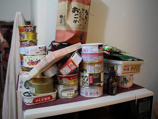 電子レンジの上にある缶詰の数々。よく見ると、かにみそやサンマなど、結構いいものだが……?