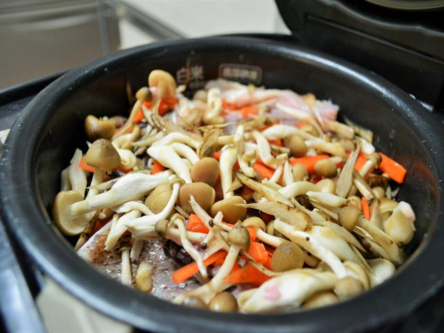 材料を全部炊飯器に入れ、スイッチオン! 写真は、間違えて鯛を先に入れてしまったもの。鯛は一度取り出して小骨を取り除く必要があるため、最後に入れよう