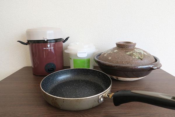 今回使用したアイテム。右上から、土鍋、一合炊き容器、格安炊飯器、そして手前がフライパン