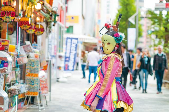 秋葉原の街を歩く神谷えりなさん。人気メンバーとなった今も、屋外を出歩く時は仮面を付けるのが仮面女子のルール