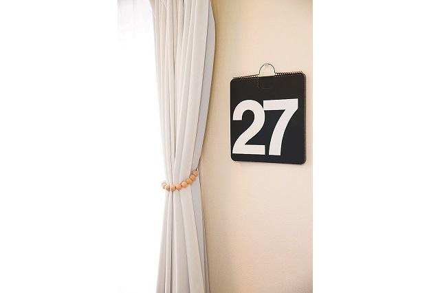 壁やカーテンが白いので、黒の背景に白文字のカレンダーがとてもよいアクセントとなっている|【インテリアコーディネート術】整理収納アドバイザーのモノトーン&シンプルな部屋作り