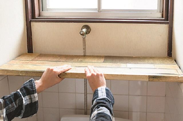 段ボールでつっぱり棒を挟むイメージ|【賃貸DIY】100均のリメイクシートと段ボールを使ってトイレに収納棚を作ろう!