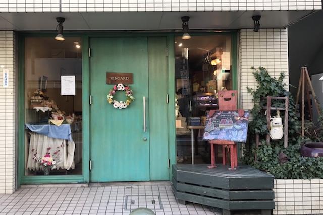 ペールグリーンのドアにフラワーリースがかわいらしい|ケーキ屋 ランギャール(王子)