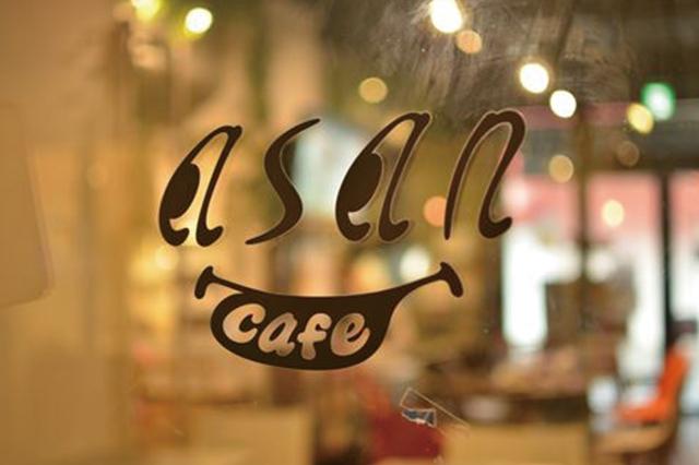 人の顔を模したキャッチ―なロゴがお出迎え|「Cafe ASAN(カフェ アサン)」(2k540 AKI-OKA ARTISAN)の入り口のガラス扉