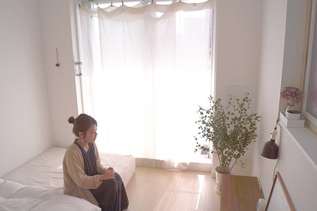 5.2畳のワンルームはスッキリしたレイアウト。カーテン代わりにしつらえた布がゆるやかで明るい空気感を醸し出す|インスタで人気!ミニマリストmamiさんに聞く断捨離のコツと快適な暮らしの持ち物とは