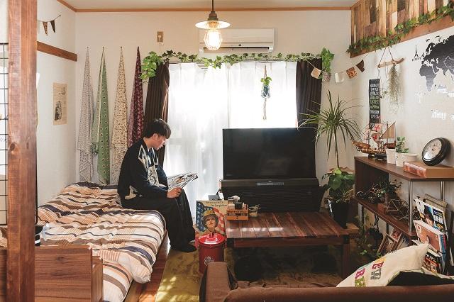 木目調の家具とグリーンで統一された、おしゃれな雰囲気の部屋でくつろぐ牛山さん|家賃3万円台の賃貸物件をDIYでアレンジ!自分らしくお得に住む方法とは?