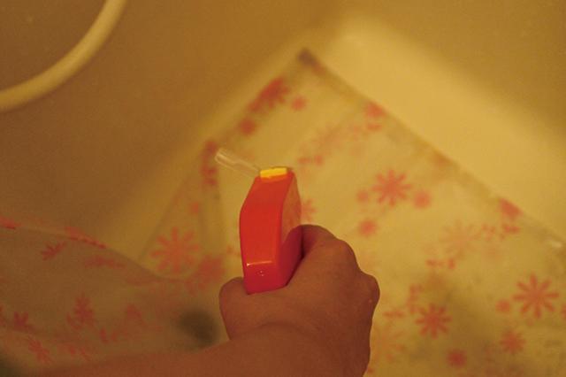 浴槽の底にシャワーカーテンの裾を広げたら、カビキラーを吹きかける|ユニットバスのシャワーカーテンのカビ対策!毎日のお手入れと掃除方法を家事・収納アドバイザーの本多弘美先生と実践