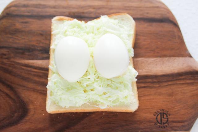 卵をのせたら、キャベツの中に押し込むように軽く指でおさえると安定する|キャベツと卵のサンドイッチの作り方|【コンビニ飯レシピ】一人暮らしの朝ごはんに!簡単ボリュームサンドイッチ3選