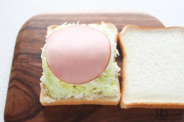 一番上にハムをのせる。ハムにもキャベツから出る水気をパンに染み込ませない役割がある|キャベツと卵のサンドイッチの作り方|【コンビニ飯レシピ】一人暮らしの朝ごはんに!簡単ボリュームサンドイッチ3選