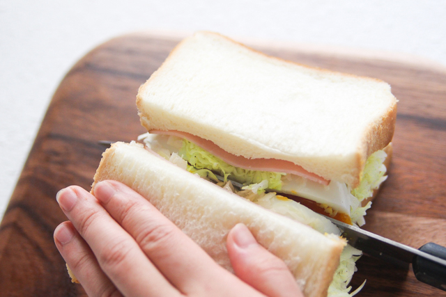 食パンをのせ、卵を横方向にカットするよう真ん中に包丁を入れる|キャベツと卵のサンドイッチの作り方|【コンビニ飯レシピ】一人暮らしの朝ごはんに!簡単ボリュームサンドイッチ3選