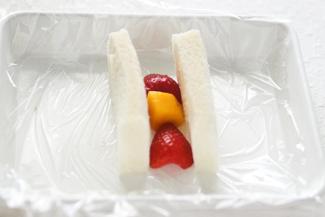 いちごの断面を下にしてパンの間におく|苺とマンゴーのフルーツサンドの作り方|【コンビニ飯レシピ】一人暮らしの朝ごはんに!簡単ボリュームサンドイッチ3選