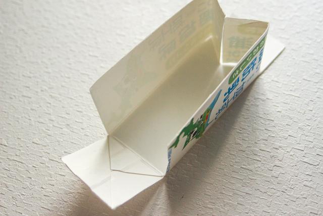 牛乳パックの上側から約5cm折り目にそって切り込みを入れ、M字になるよう折り曲げてテープで固定する|鯉のぼりの押し寿司の鯉のぼり型の作り方|コンビニで買える食材で作れる!こどもの日のメニューにおすすめのレシピ!簡単&かわいい鯉のぼりの押し寿司でお祝いしよう