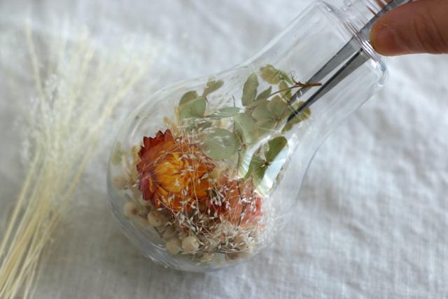 電球型のビンには、花材をギュッと押し込んで|簡単おしゃれなハーバリウムの作り方。部屋のインテリアに枯れない花を取り入れよう