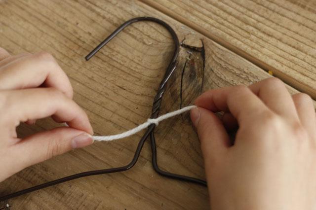 まずはワイヤーのねじり始め部分に、アクリル毛糸を結びつけよう|【賃貸DIY】100均ワイヤーハンガーをおしゃれにリメイク!もこもこハンガーの作り方