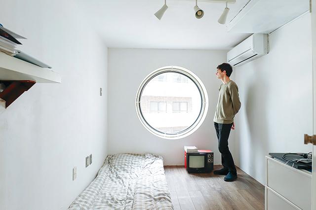歴史的デザイナーズ物件「中銀カプセルタワービル」の室内で窓の外を見つめるテンシャンさん