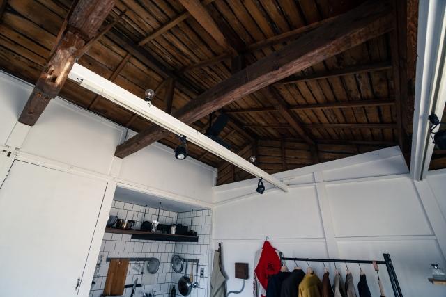 頑丈な梁の姿がそのまま見える屋根。ライトレールには照明が取り付けられていて、下方だけでなく上方も照らす