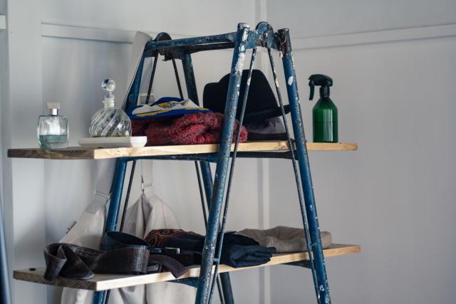 脚立に横板を渡しただけのシンプルなオープンラック。脚立には、壁を塗った時についてしまったという白いペンキの跡が