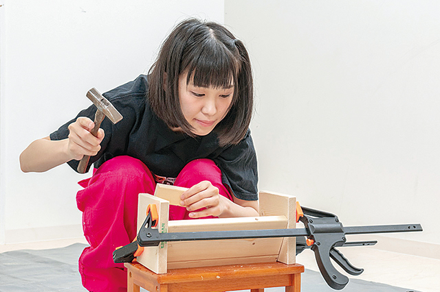 仮面女子・陽向こはるが挑戦するDIY作品「ミニブックスタンド」の作り方:バークランプで棚受けと側板を仮留めした状態で、棚受けの角度をとんかちで叩いて微調整