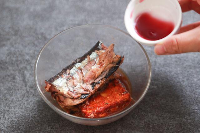 ワインが進む簡単&絶品おつまみレシピ・さんまのトマト煮込みの作り方:さんまの蒲焼の煮汁、トマトスープ、さんまの身の順で耐熱容器に移し、最後に赤ワインを加える