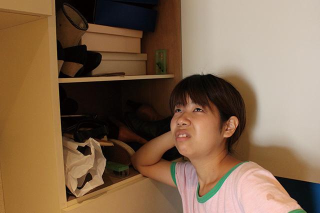 汚い下駄箱にひじをついてぼーっと下駄箱の収納について考えるCHINTAI編集部の木村