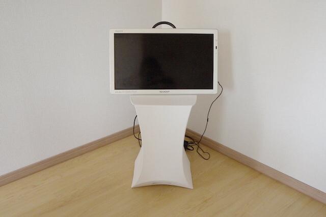 たためるスツールに乗ったキャリングハンドル付きの液晶テレビ