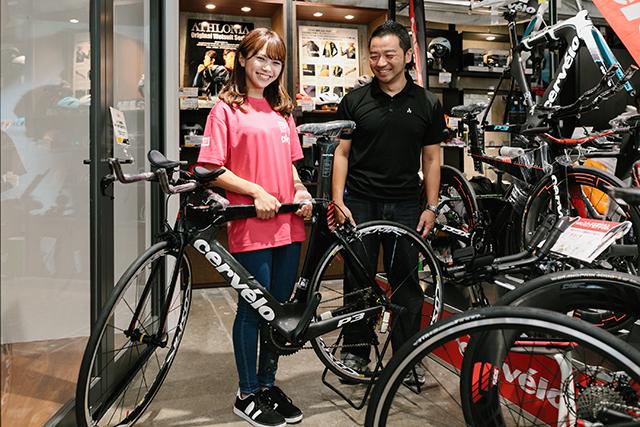 自転車を持ち上げるNMB48・磯佳奈江さんの様子