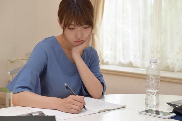 家計簿をつけながら悩んでいる女性