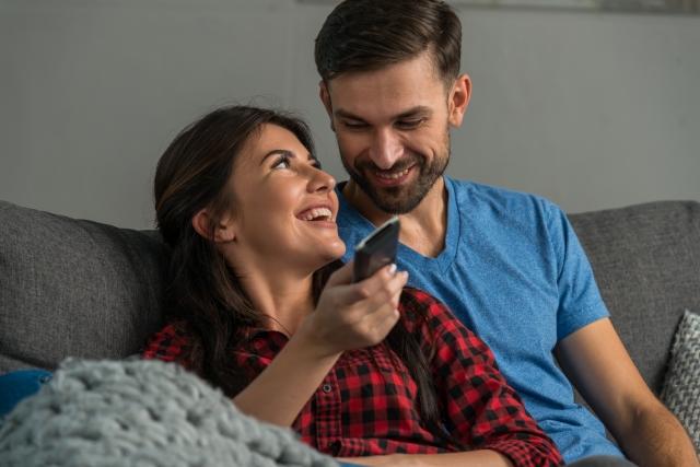 テレビを見ながらくつろぐカップル