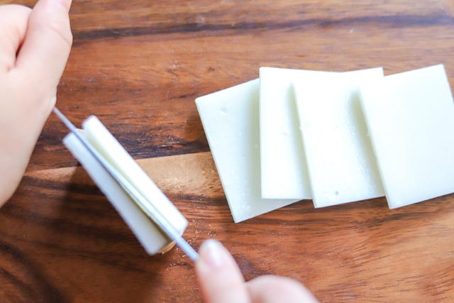 余ったお餅で作る餅カレーラザニアのレシピ工程:餅を横に立てて、まっすぐ包丁を下ろす