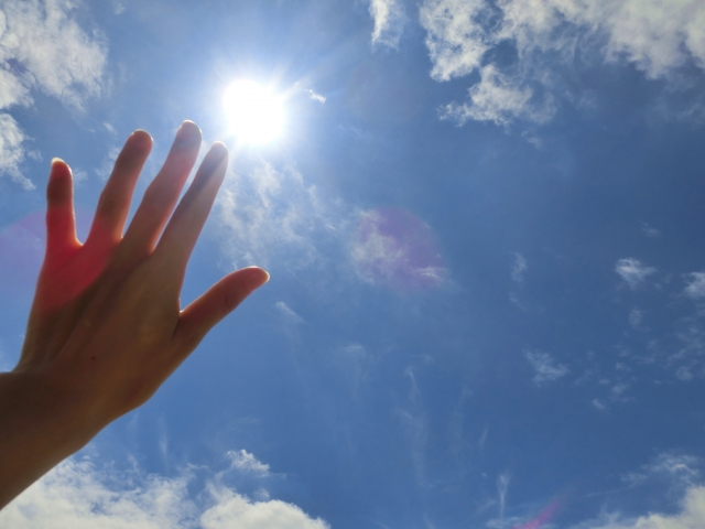 空に手をかざす人