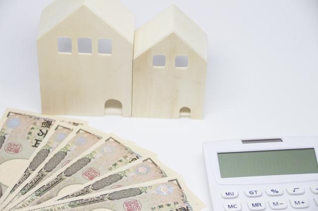家賃を計算するための電卓と家の模型