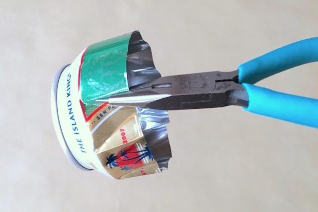 防災アイテム・アルミ缶コンロの作り方の工程:ラジオペンチでアルミ缶にくぼみをつけている様子