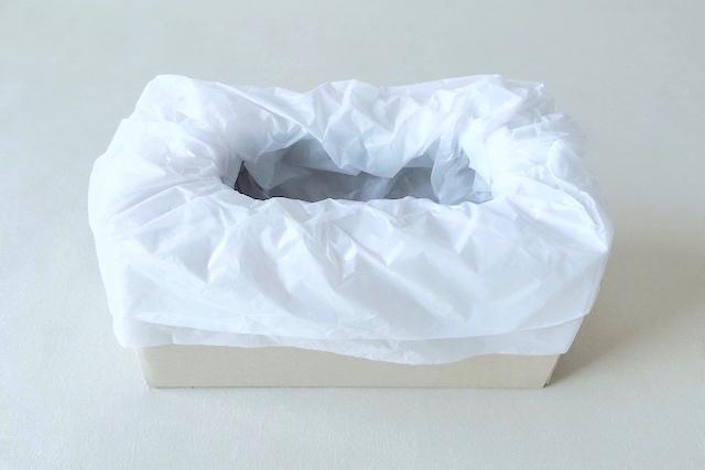 防災アイテム・段ボール簡易トイレの作り方の工程:段ボールにあけた穴にポリ袋をセットする