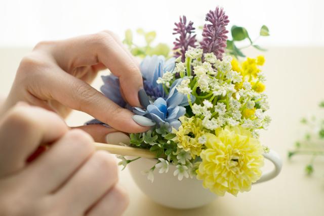 100均の材料で作る造花アレンジメントのレシピ:造花を入れた器の隙間に割り箸を使ってグリーンを詰めていく