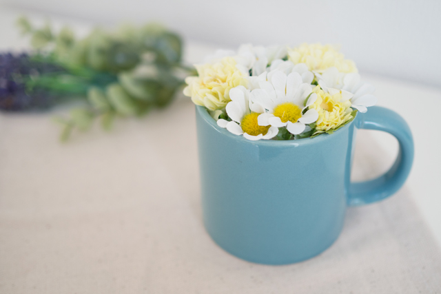 水色のマグカップに白い造花を詰めた造花アレンジメント