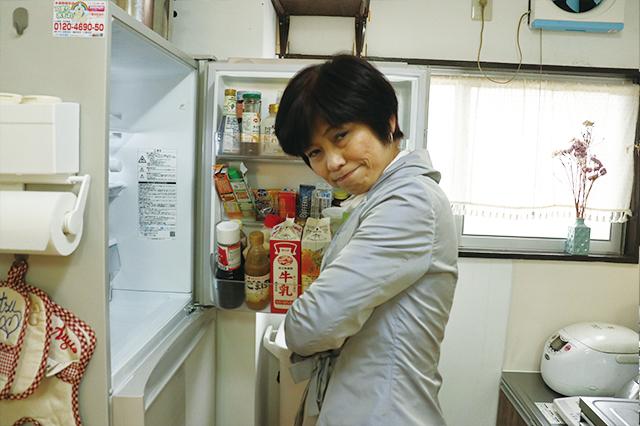 冷蔵庫の前で腕組みする本多先生
