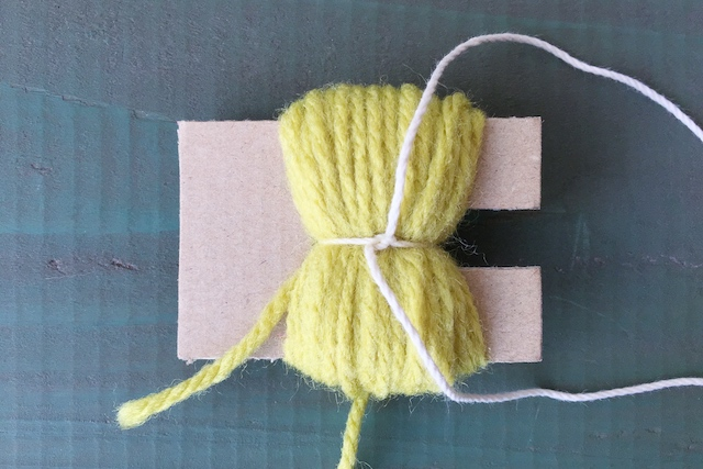 ポンポンの作り方:巻いた糸を切り込みのあるところまでズラし、たこ糸で結ぶ