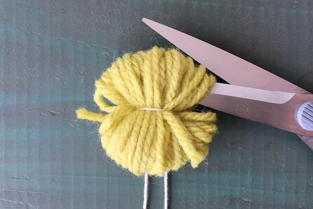 ポンポンの作り方:糸を厚紙から外して両端の輪をカットする