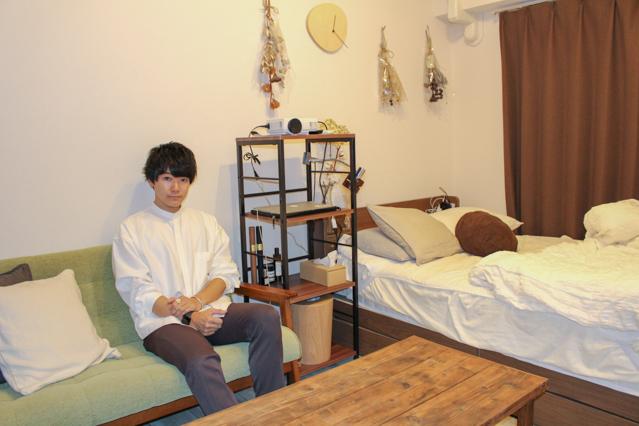 緑色のソファーに座るシンプリストのエヌケンさんとシンプルな一人暮らしのお部屋