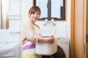 洗濯物カゴを抱えている女性