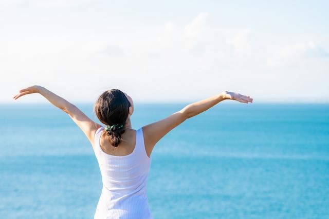 海で両腕を広げている女性